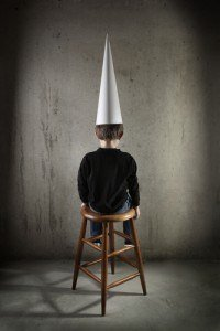 embarrassed child with dunce cap on